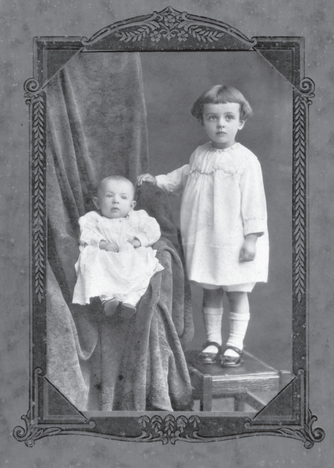Early 1900s photo portrait of baby and toddler in decorative framing.
