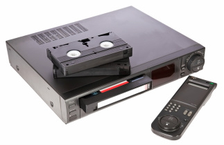 A home VCR with remote and three VHS videotapes.