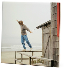 Photo print on tile - a boy balances on the railing of boathouse on beach.