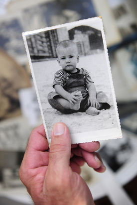 An old black and white photograph of a baby boy is held up by the hand of an unseen observer with a backdrop of more and more old photos in a pile.